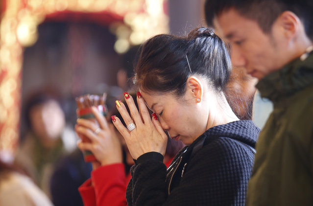 Chinese visitors pray during the celebration of the Lunar New Year at a temple in Hong Kong, Monday,