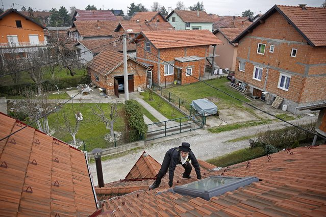 Dajana Djuric, 25,who has worked as a chimney sweep since the age of six, climbs a roof of a house t