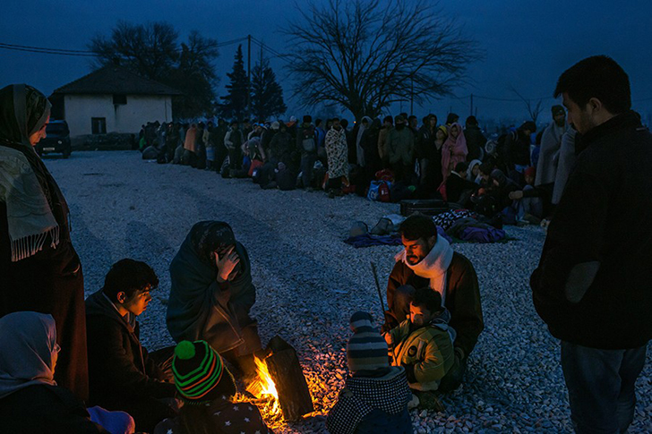 Семья беженцев из Сирии греется у костра, пока другие стоят в очереди на регистрацию в приемном лаге