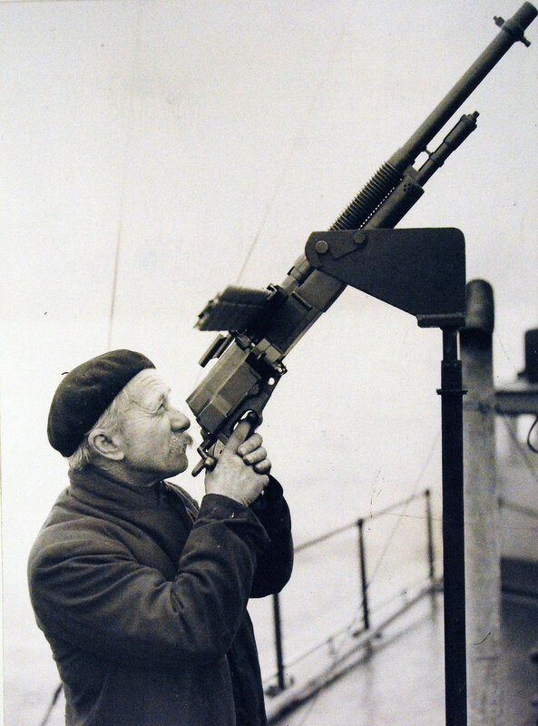 Moy Jones, who has been at sea for over 50 years practicing firing a Hotchkiss gun on board an Instructional Motor Launch at a Northern Port, Feb 1942.
