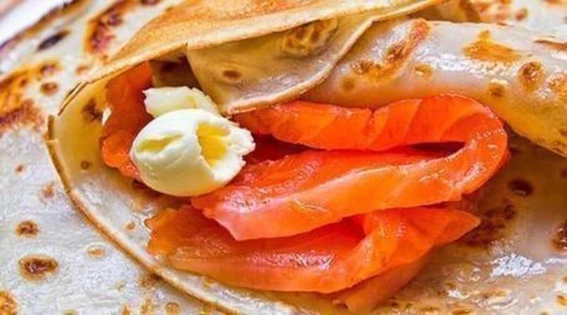 Мягкий сливочный сыр намазать на каждый блинчик, на край уложить пластик слабосоленой семги (лосося,