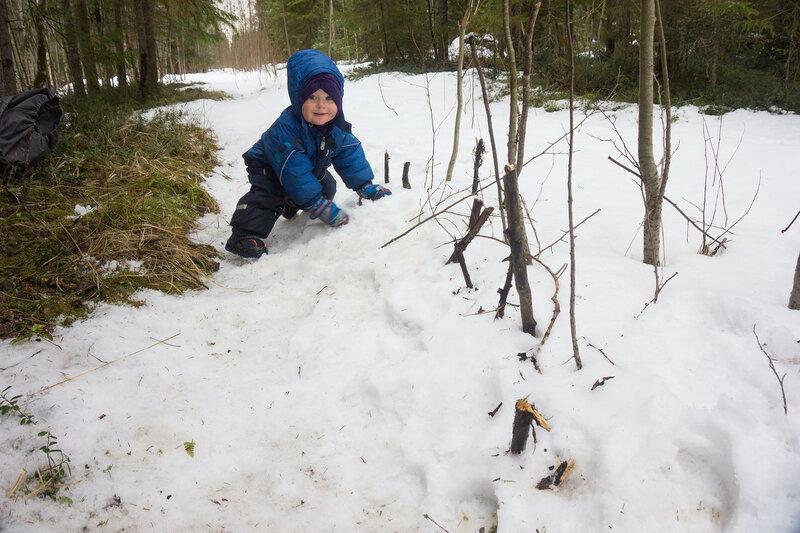 ребенок играет с палочками в лесу в снегу