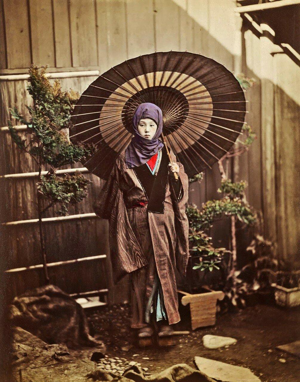 Одетая по зимнему японка с зонтиком