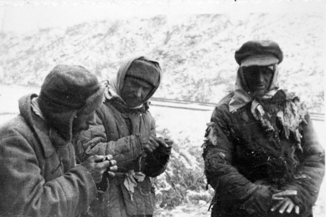 1941. Советские военнопленные пытаются отогреть руки