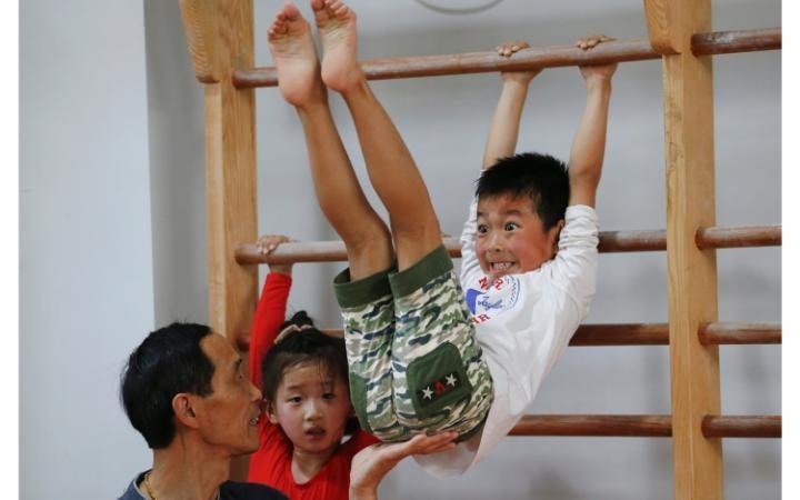 Девочки выполняют стойку на руках на занятии по гимнастике в спортивной школе Shanghai Yangpu Youth