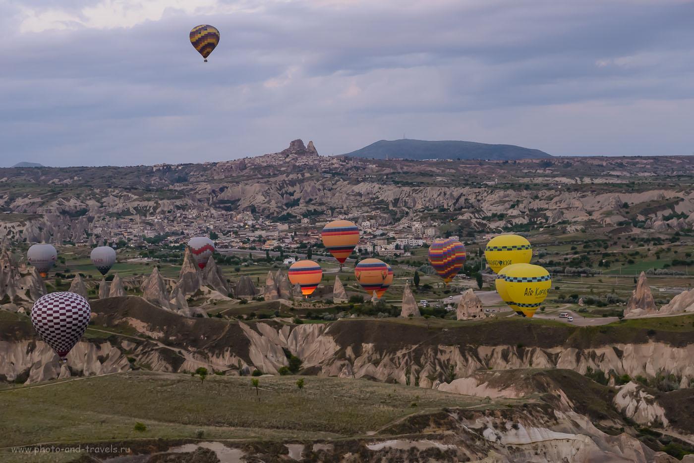 Фото 1. Воздушные шары в небе Каппадокии. На заднем плане – поселок Гёреме, а вдали – «башня» замка Учхисар. Отзывы туристов о путешествии по Турции. Снято на полнокадровый фотоаппарат Nikon D610 с объективом Nikon 24-70mm f/2.8 со следующими настройками: выдержка 1/125 секунды, экспокоррекция 0EV, диафрагма f/8.0, ISO 5000 единиц, фокусное расстояние 70 мм.