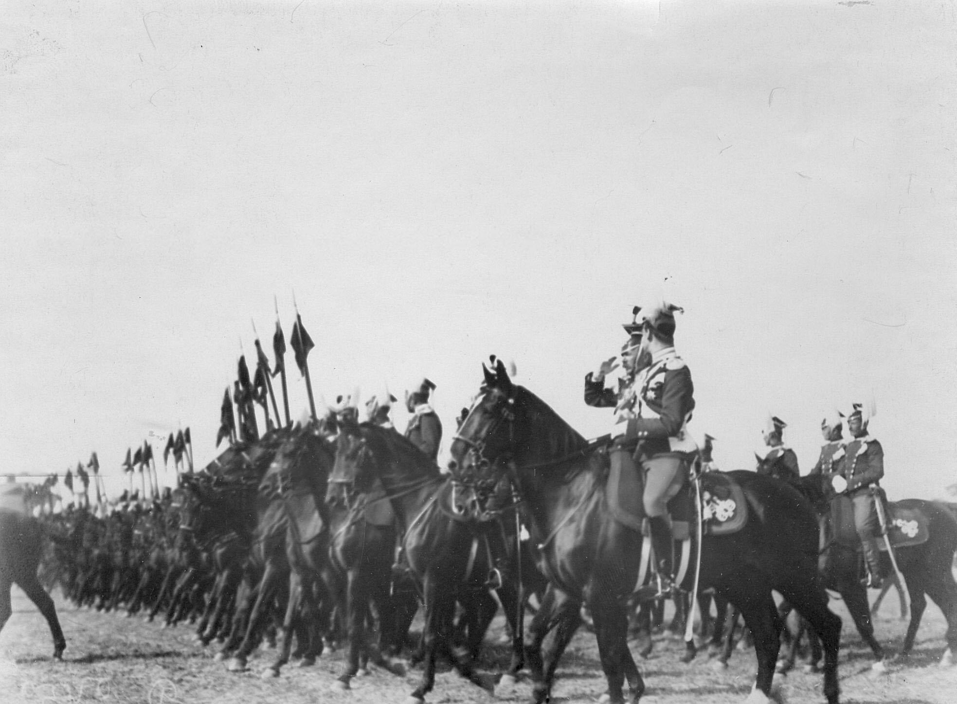 Уланы полка проходят церемониальным маршем мимо принимающих парад в день празднования 250-летнего юбилея полка. Слева на фланге - великий князь Михаил Александрович
