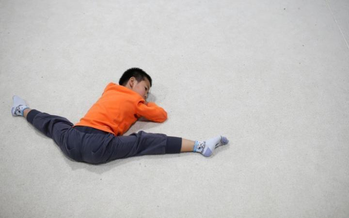Воспитанник надевает шлем перед тренировкой по фехтованию в спортивной школе в Пекине.