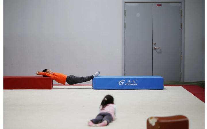 Дети выполняют стойку на руках на занятии по гимнастике в спортивной школе Shanghai Yangpu Youth Ama