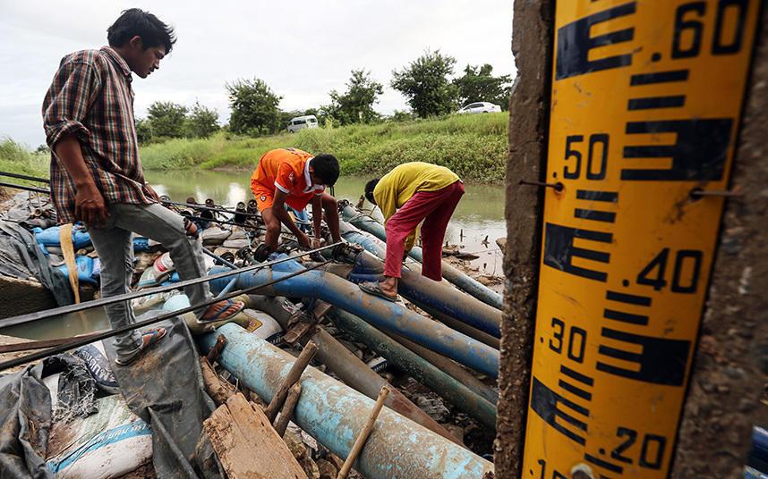 6. Фермеры налаживают водяные насосы возле шлюза оросительного канала в провинции Чайнат. Уровень во