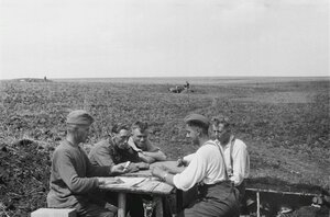 После боевых действий. Пятеро солдат играют в карты посредине поля