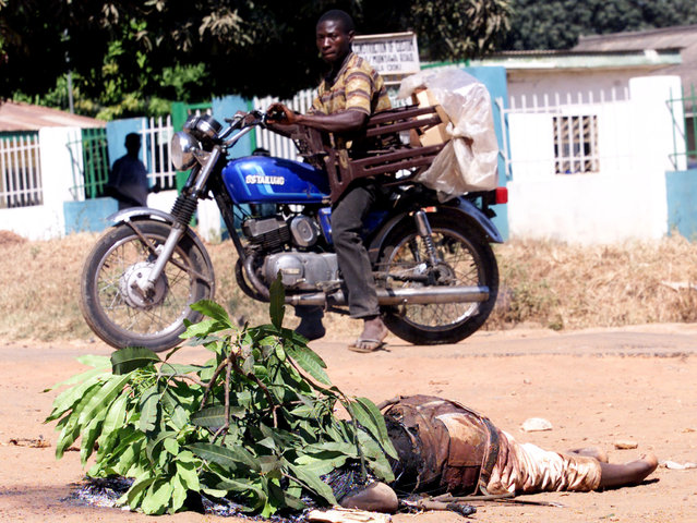 Nigerian men on A motorcycle drive by a body in the northern city of Kaduna on November 22, 2002, af