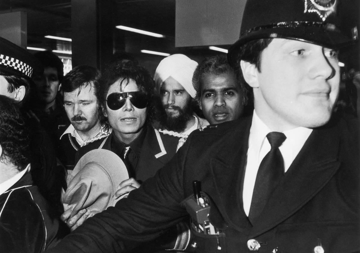Полицейский проводит Майкла через толпу во время его тура в Лондоне в 1985 году. (Dave Hogan/Getty I