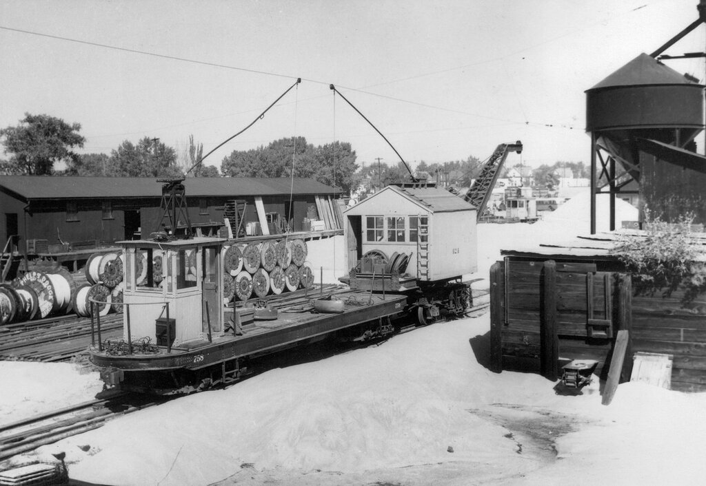 Denver Tramway Corporation work cars 758 and 424 in the Alameda yard in Denver, Colorado. Car 758 has a crane. 1940s
