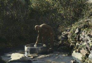 Мужчина сван черпает воду из родника