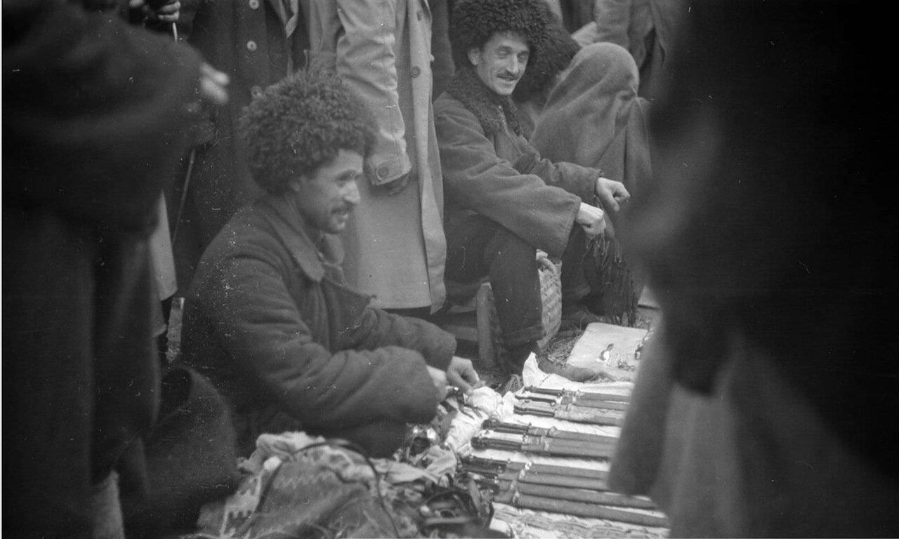 Мужчина, торгующий холодным оружием на деревенском рынке