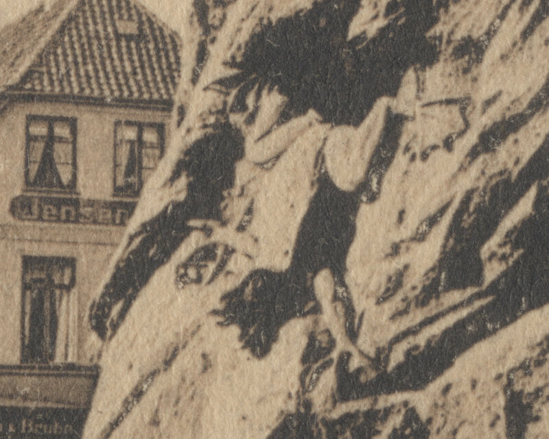 Der Wasserspeier in Gestalt eines Frosches des zerstörten Brunnens mit dem Gebäude von Jensen & Bruhn im Hintergrund