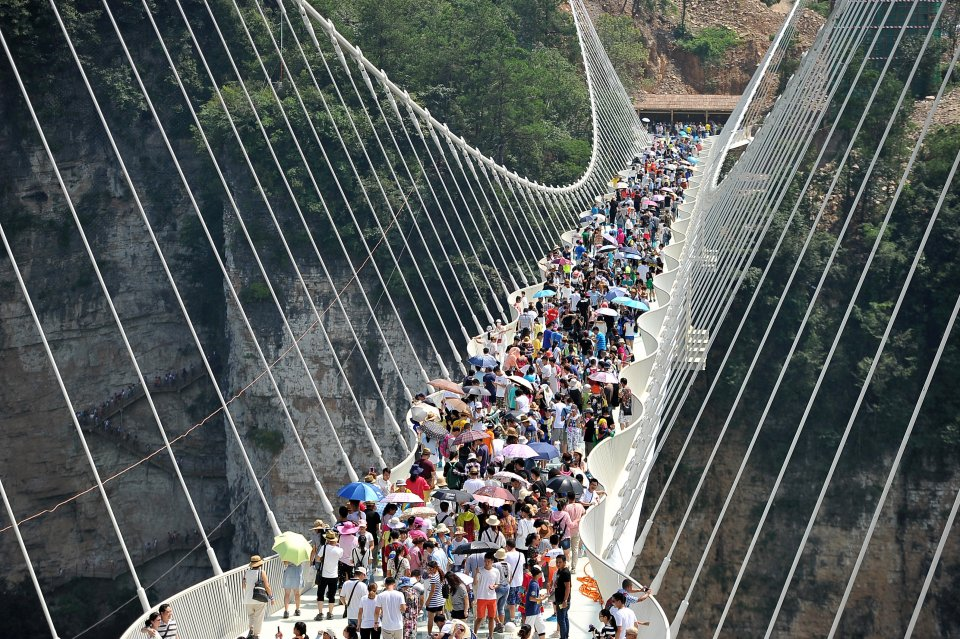 People visit a glass bridge at a gorge as it opens to public in Zhangjiajie