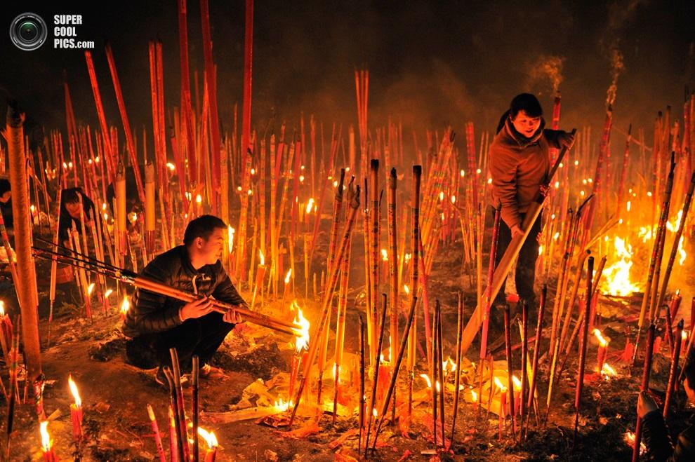 Прихожане поджигают благовонные палочки в храме Дафо,Чунцин, Китай.(REUTERS/Stringer)