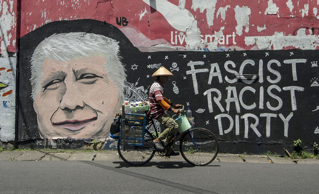 A man cycles past graffiti condemning US Republican presidential nominee Donald Trump, on a street i