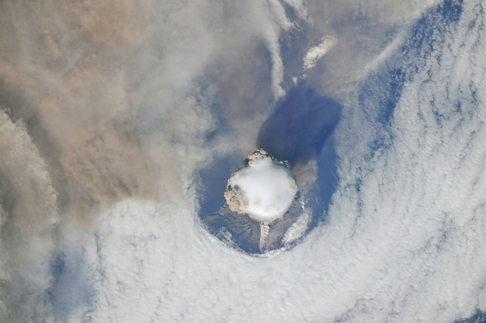 2) Вид пика вулкана Сарычева, на котором видно больше деталей, круглое отверстие в облаках вокруг ос