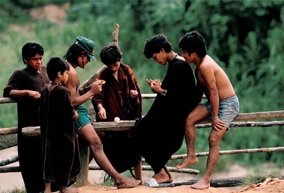 13. Мальчишки племени делают расчески из стеблей бамбука недалеко от реки Аммония в Бразилии. (&copy