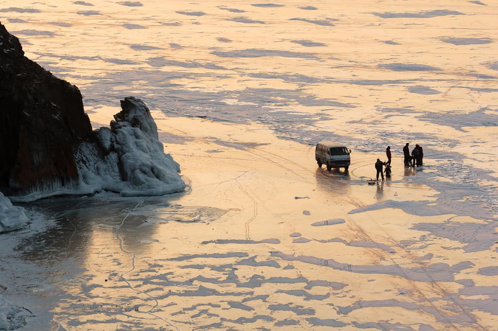 Несмотря на толщу льда в несколько метров, который выдерживает вес машины, рыбаки сверлят лунки для