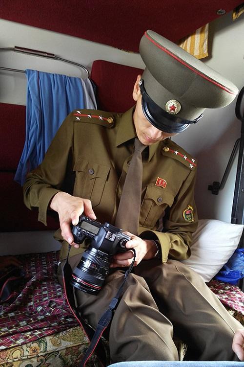 9. Офицер таможенной служды проверяет цифровую камеру пассажира в поезде, следующего из Москвы в Пхе