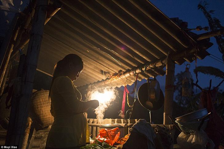 Сяо Цзе готовит ужин на деревянной кухне в доме своих свекра и свекрови, где они живут все вместе.