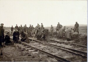Солдаты во время подбивки перевода балластом.