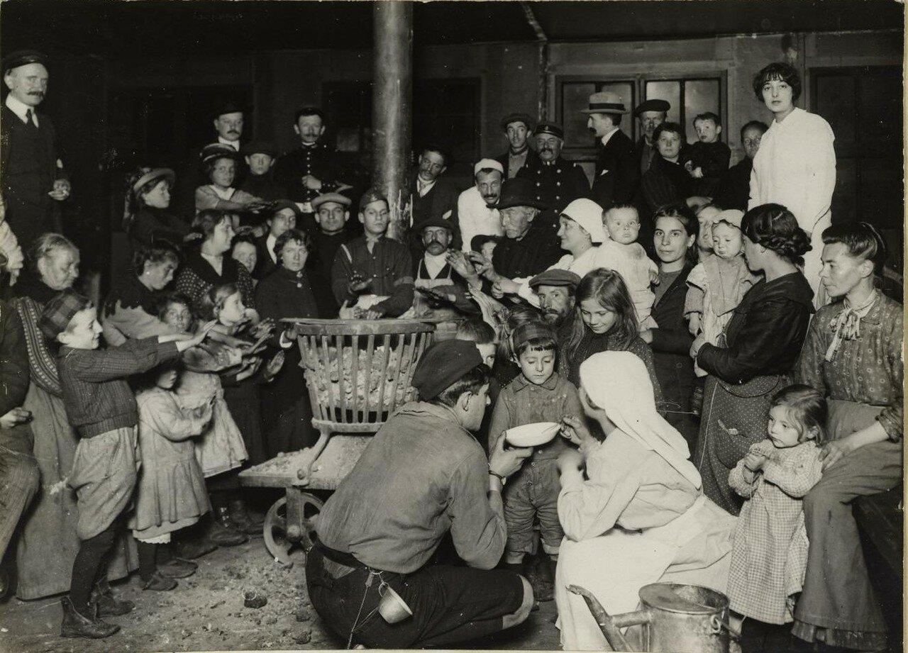 1914. Беженцы на Северном вокзале. Сильные холода заставили установить огромную жаровню, вокруг которой все и сидят. 10 октября
