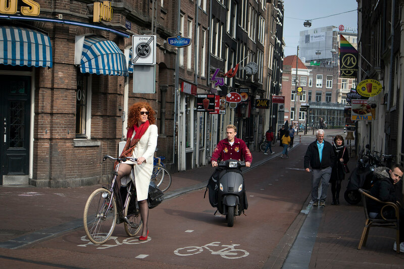 Girls ride bicycles in a northern europe city