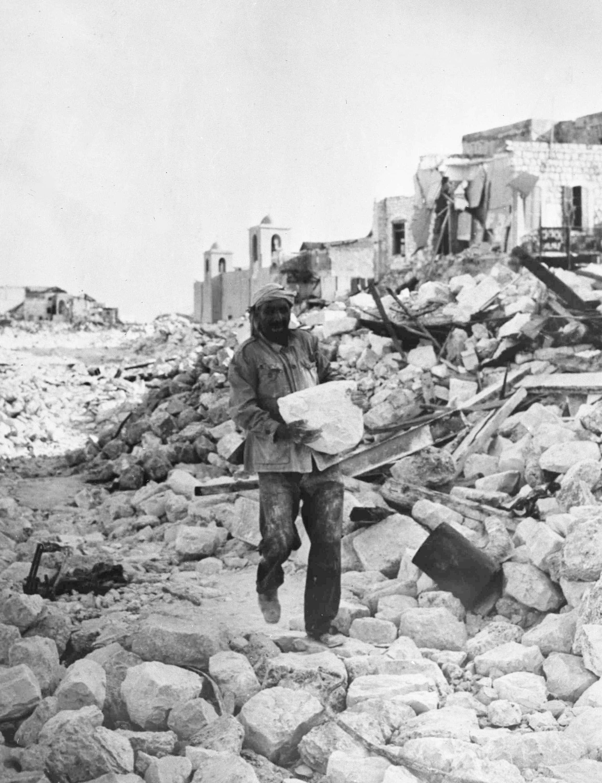 Арабский рабочий является одним из многих, кто помогает еврейским властям в Хайфе расчищать завалы, оставшиеся после уличных боёв. 8 ноября