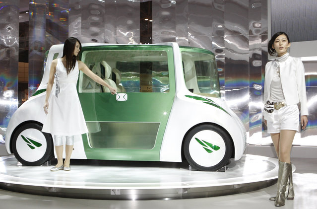 Models pose with Toyota Motor Corp's RiN concept vehicle, a car designed to promote healthy liv