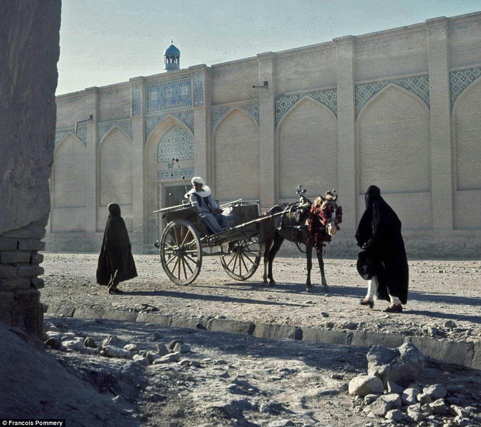 Женщины с покрытой головой у повозки в Герате — третьем крупнейшем городе Афганистана.