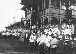 Зрители на трибунах ипподрома перед началом скачек; на балконе  император Николай II и члены императорской фамилии