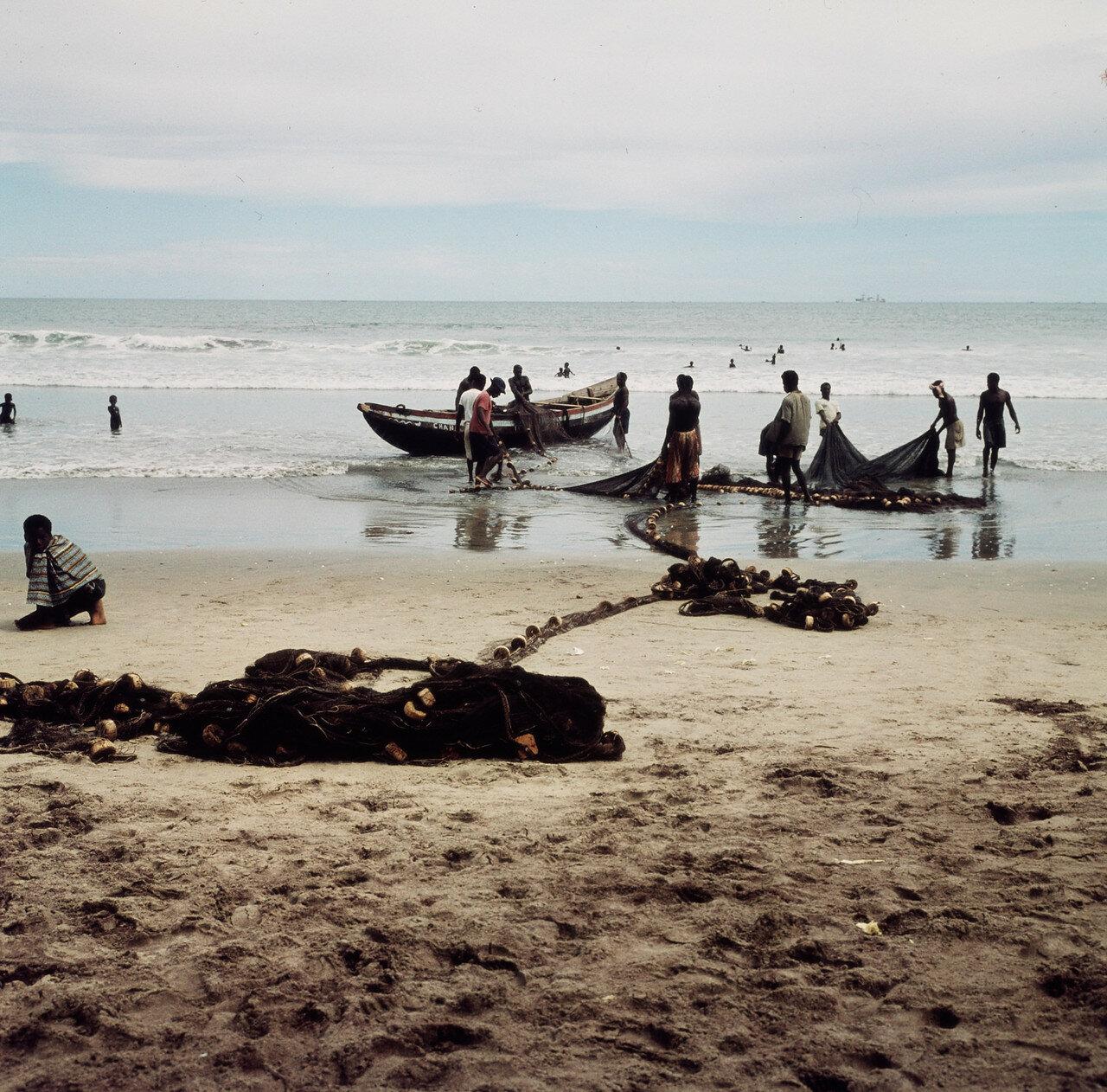Рыбак с прибойной шлюпки и сеть на берегу. 28 марта
