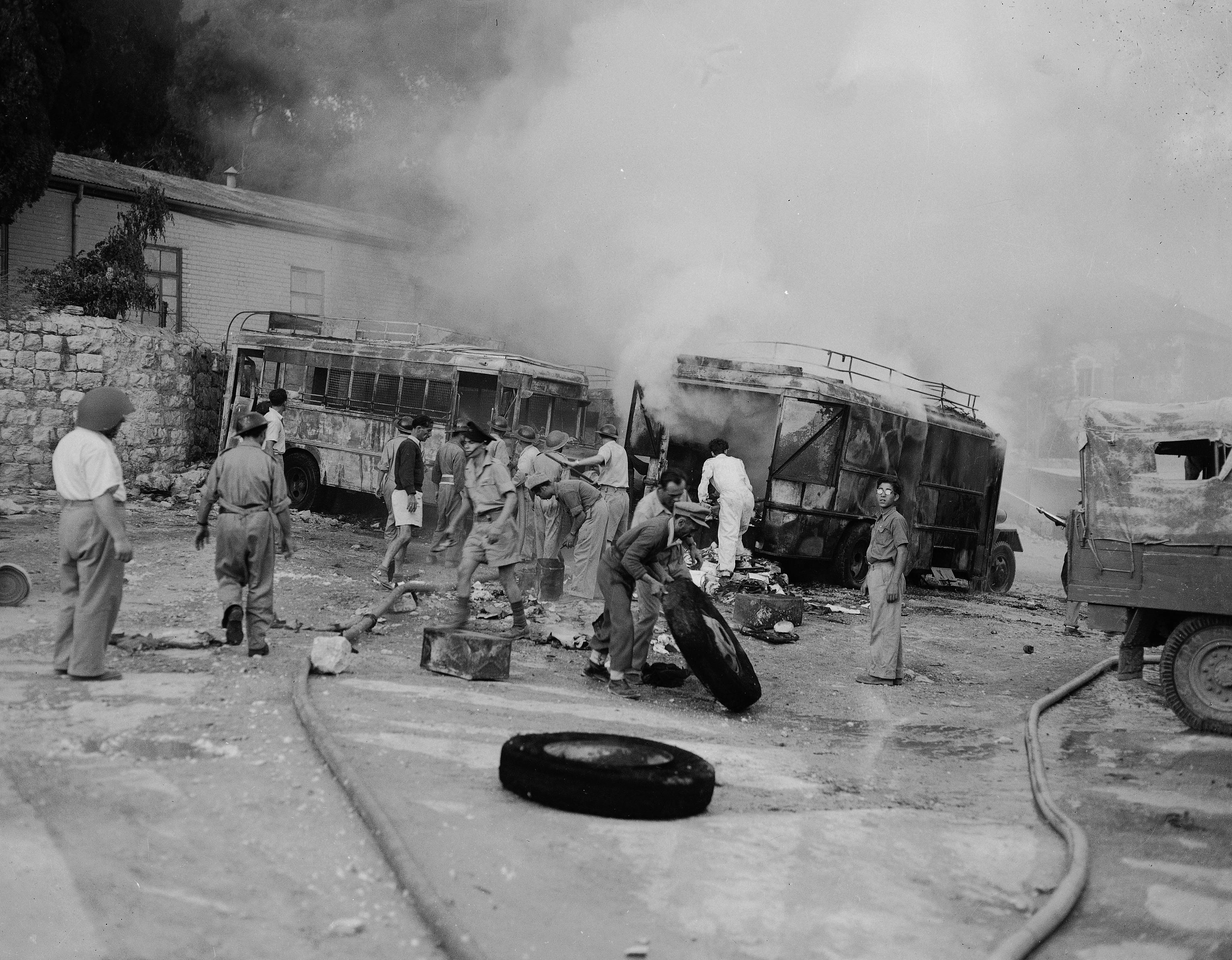 Еврейские пожарные участвуют в спасательной операции, поскольку дым по-прежнему поднимается от двух автобусов на автостоянке по Яффо-роуд в Иерусалиме, которая была обстреляна арабскими зажигательными минометными снарядами, 12 июня