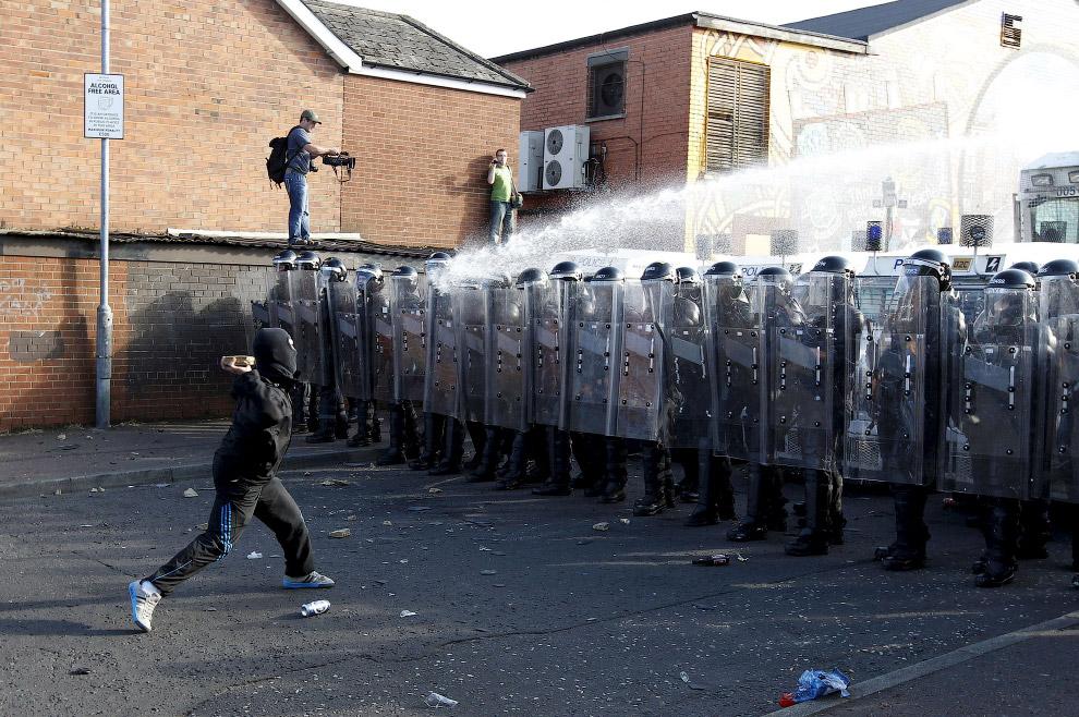 7. Я вам покажу! Местные жители противостоят силам безопасности на улице в городе Урумчи, Китай