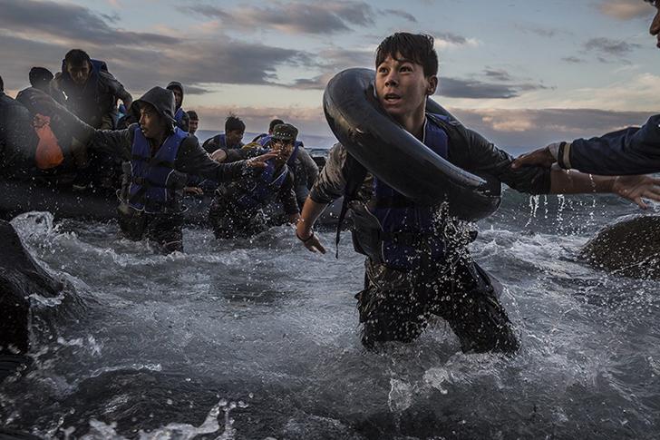 Пережив шторм и сильный ветер на море в Турции, мигранты прибывают на резиновых плотах к зубчатым бе