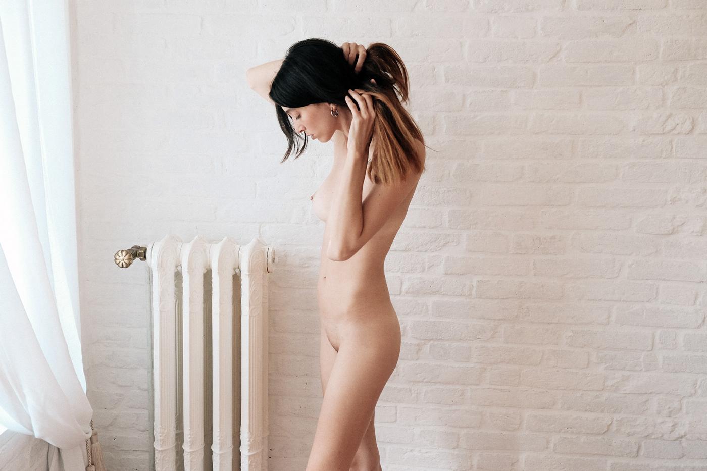 Белая крашеная кирпичная стена и голая девушка / фото Adolfo Valente
