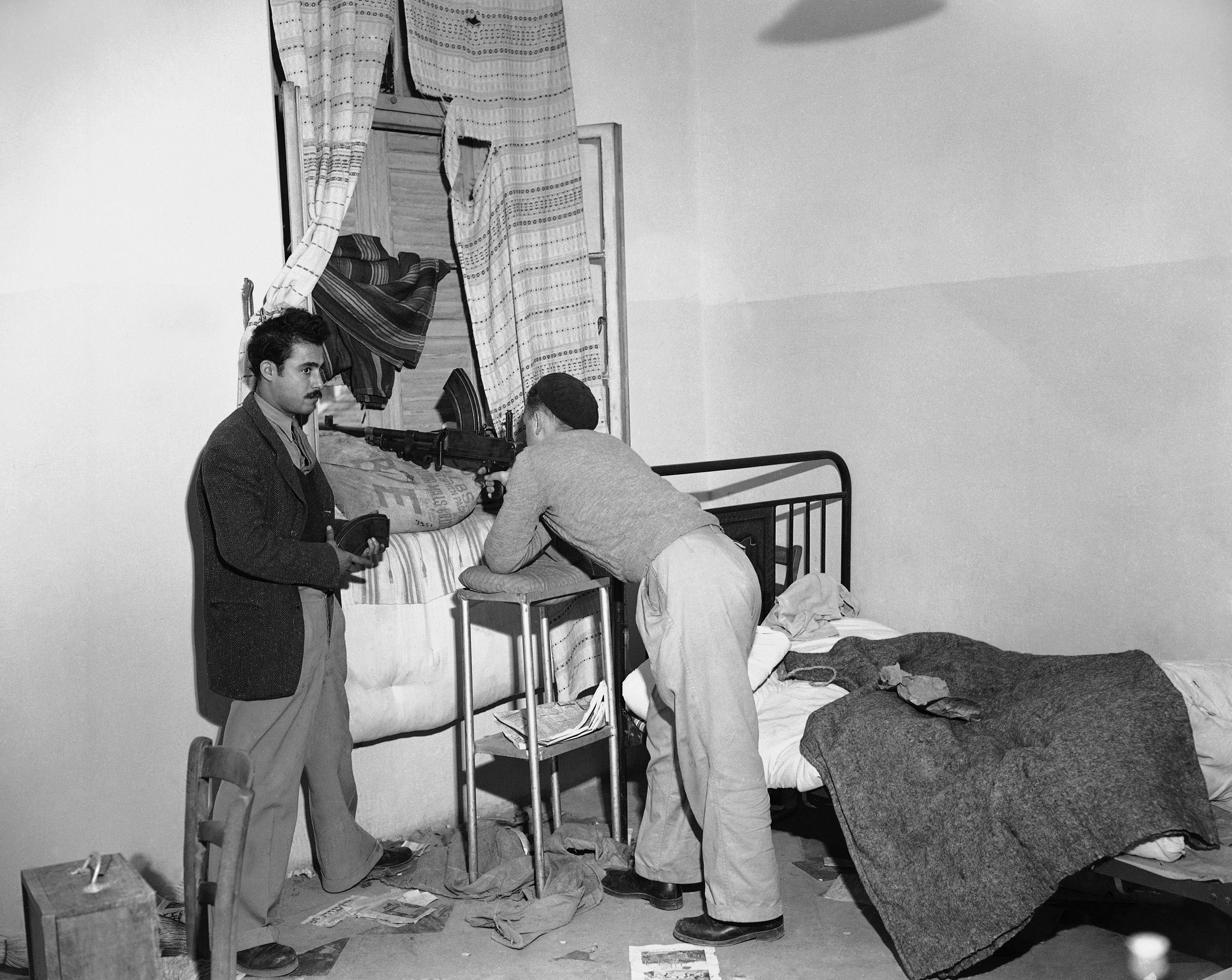 Два еврея из Иргун, вооруженные ручным пулемётом Брена и револьвером охраняют дом в квартале Маншиа на границе Тель-Авив-Яффо. 8 января