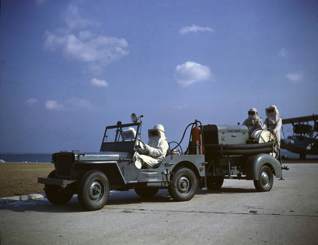 Four U. S. Coast Guard firefighters riding in a jeep and on the high pressure water pump and hose it is towing, 1943.