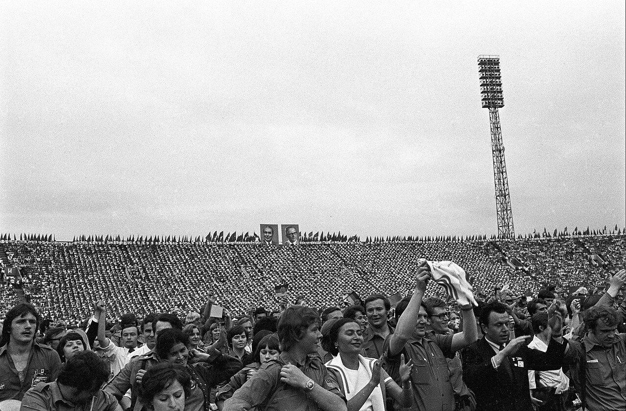 Зрители на трибунах и участники на арене стадиона