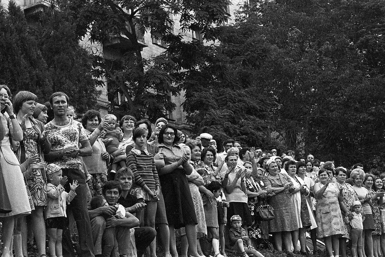 Зрители на обочине дороги смотрят прохождение колонны участников Фестиваля