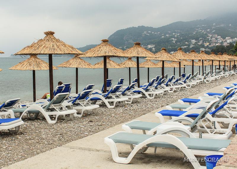 Лежаки на пляже укрытые зонтами