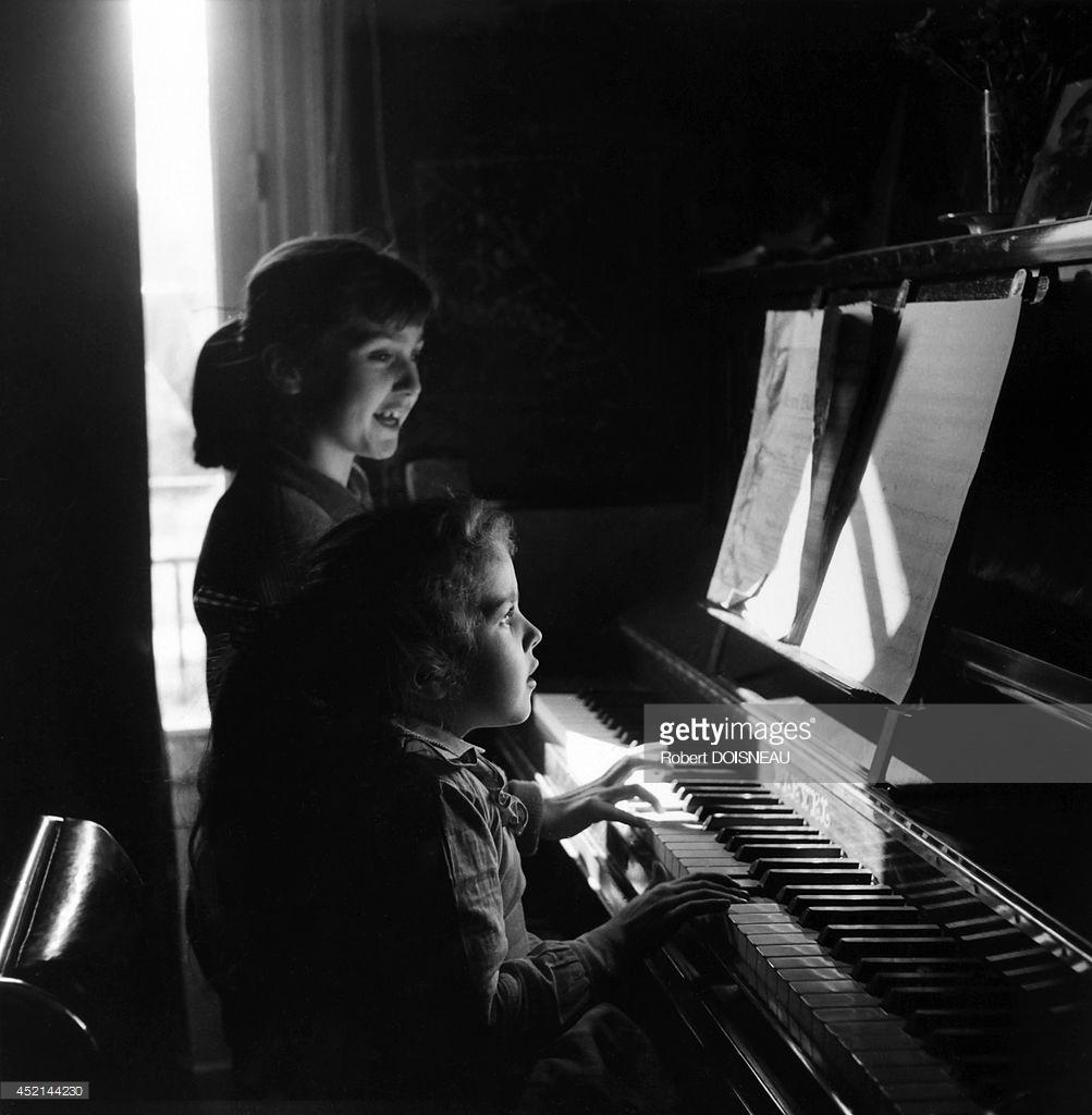 1954. Двое детей играют на фортепиано. Париж