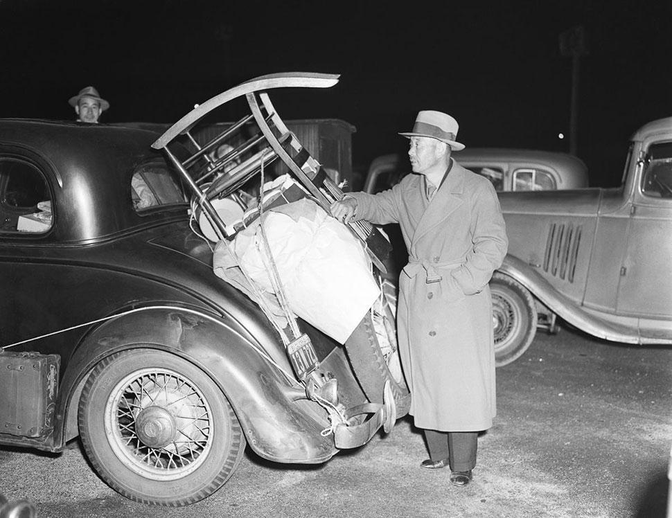 Мужчина из Пасадены укладывает свои вещи в машину, чтобы отправиться в лагерь Манзанар.