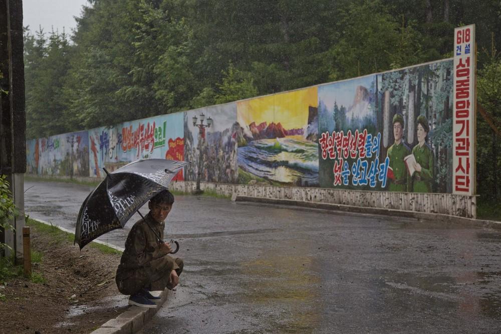 6. Кореец укрывается от дождя рядом с длинной стеной с пропагандистскими плакатами в городе Самиджон