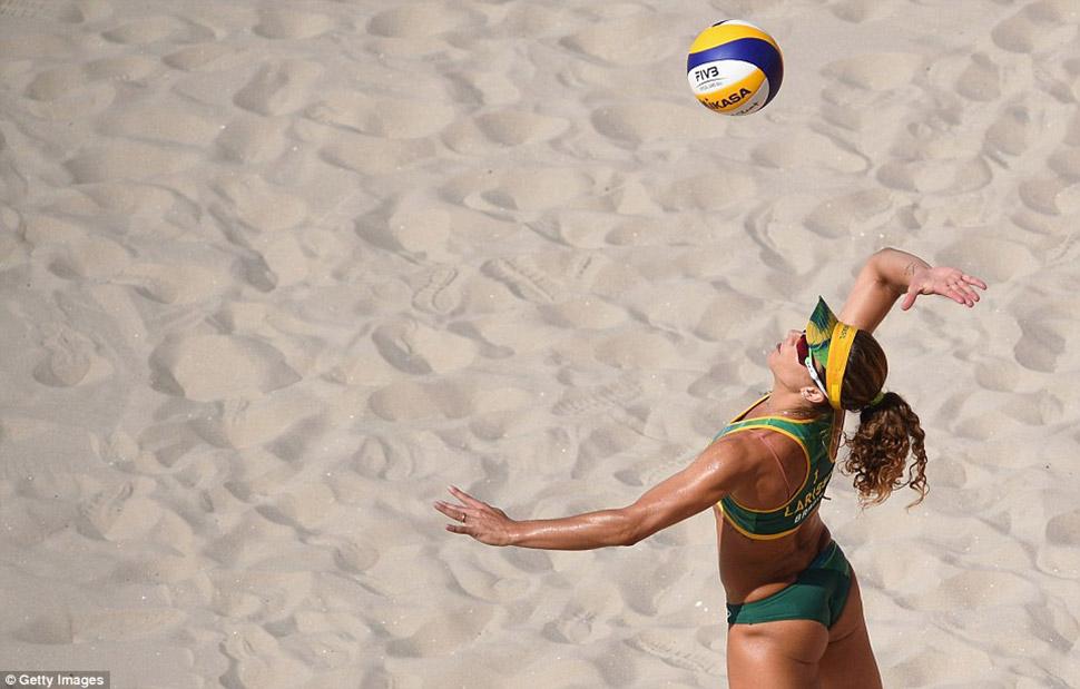 Ларисса Франка Маэстрини из бразильской команды подает мяч против Екатерины Бирловой и Евгении Уколо